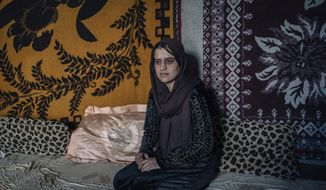 In this Jan. 11, 2017 photo, 23-year-old Perwin Ali Baku poses for a portrait inside the tent she shares with her family at Karbato camp for civilians displaced by war in Iraq. She recently escaped Islamic State militant captivity alongside her young daughter. A new psychological trauma institute is being established at the university of Dohuk in Iraq, the first in the entire region. The program will train local mental health professionals to treat Islamic State victims, including thousands of Yazidi women and children. (AP Photo/Alice Martins)