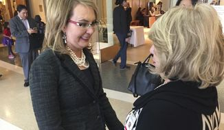 Former U.S. Congresswoman and mass shooting survivor Gabrielle Giffords, left, greets an admirer at the Statehouse in Santa Fe, N.M., on Wednesday, Feb. 22, 2017. Giffords and her national gun-safety advocacy group Americans for Responsible Solutions are trying to build support for bills that would expand background checks on private firearms sales in New Mexico and remove guns from domestic violence situations where a restraining order has bee issued. (AP Photo/Morgan Lee)