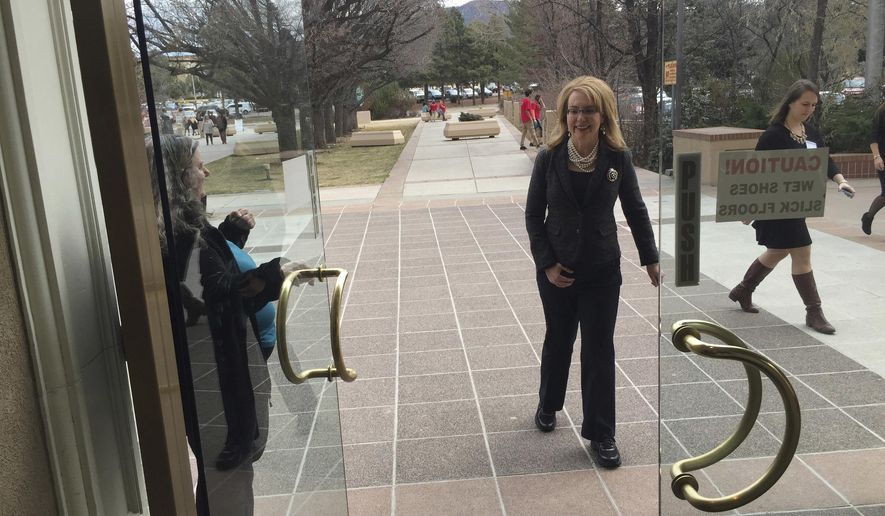 Former U.S. Congresswoman and mass shooting survivor Gabrielle Giffords enters the Statehouse on Wednesday, Feb. 22, 2017, in Santa Fe, N.M. Giffords and her national gun-safety advocacy group Americans for Responsible Solutions are trying to build support for bills that would expand background checks on private firearms sales in New Mexico and remove guns from domestic violence situations where a restraining order has bee issued. (AP Photo/Morgan Lee)
