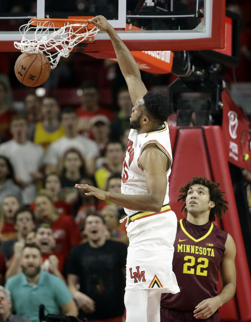 Maryland forward Damonte Dodd dunks on Minnesota center Reggie Lynch during the first half of an NCAA college basketball game, Wednesday, Feb. 22, 2017, in College Park, Md. (AP Photo/Patrick Semansky)