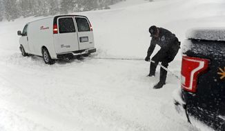 A Nevada Highway Patrol officer helps a stuck motorist on the Mt. Rose Highway near Reno, Nev., Tuesday, Feb. 21, 2017. One of the strongest in a series of winter-long storms pummeled the Sierra Nevada with another 3 feet of snow on Tuesday, dumping triggering an avalanche that buried a major highway near Lake Tahoe in 20 feet of snow and dumping record-breaking rain on Reno for the second day in a row. (Jason Bean/The Reno Gazette-Journal via AP)