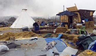 Refuse remains in the Dakota Access pipeline opponents' main protest camp as a fire burns in the background in southern North Dakota near Cannon Ball, N.D., on Wednesday, Feb. 22, 2017, as authorities prepare to shut down the camp in advance of spring flooding season. (AP Photo/Blake Nicholson)