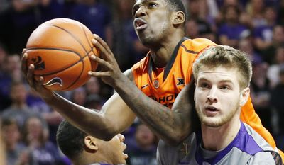 Oklahoma State guard Jawun Evans shoots over the shoulder of Kansas State forward Dean Wade (32) during the first half of an NCAA college basketball game Wednesday, Feb. 22, 2017, in Manhattan, Kan. (Bo Rader/The Wichita Eagle via AP)