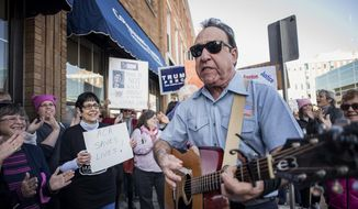 "John Spasaro, with Milwaukee's Sing A Song Telegram, performs a version of ""Please, Mr. Postman"" with altered lyrics addressed to House Speaker Paul Ryan outside of Ryan's office on Main Street in downtown Janesville, Wis., Wednesday, Feb. 22, 2017. (Angela Major/The Janesville Gazette via AP)"