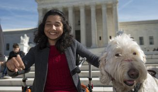 FILE - In this Oct. 31, 2016 file photo, Ehlena Fry of Michigan, sits with her service dog Wonder, while speaking to reporters outside the Supreme Court in Washington. The Supreme Court says a lower court should take another look at whether Fry, who has cerebral palsy can sue Michigan school officials over their refusal to let her to bring a service dog to class.  (AP Photo/Molly Riley, File)