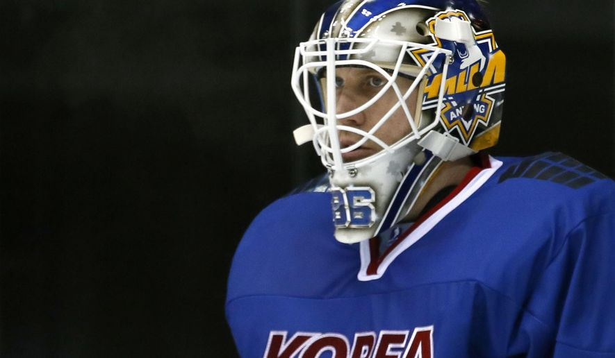 In this Feb. 22, 2017 photo, South Korea's goalkeeper Matt Dalton watches teammates' play in their ice hockey men's top division match against Kazakhstan at the Asian Winter Games in Sapporo, northern Japan. Growing up in rural southern Ontario, Dalton never figured that his career path in professional hockey would take him to South Korea. Dalton, along with a handful of other North American players, has acquired South Korean citizenship and is a key member of the men's national ice hockey team as it prepares to take on the world's best as host of the 2018 Winter Olympics. (AP Photo/Shuji Kajiyama)