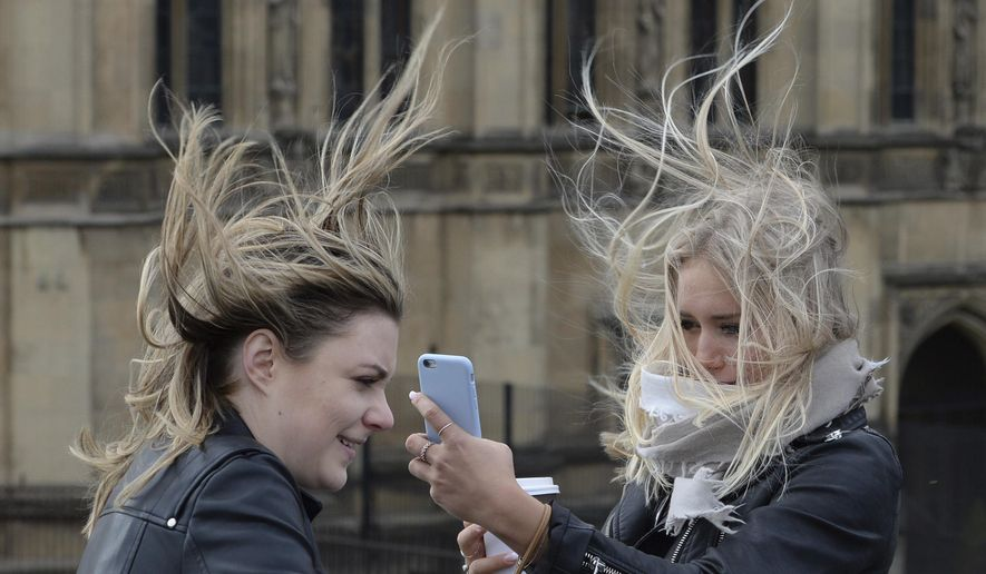 Women attempt to take a selfie amid strong winds on Westminster Bridge, London, Thursday, Feb. 23, 2017. Flights have been cancelled and commuters were warned they faced delays after Storm Doris reached nearly 90mph. (Stefan Rousseau/PA via AP)
