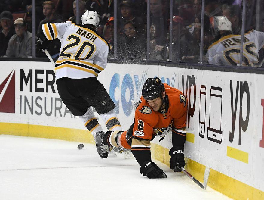 Anaheim Ducks defenseman Kevin Bieksa, right, goes down as Boston Bruins center Riley Nash takes the puck during the first period of an NHL hockey game, Wednesday, Feb. 22, 2017, in Anaheim, Calif. (AP Photo/Mark J. Terrill)