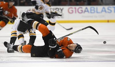 Anaheim Ducks defenseman Korbinian Holzer, front, of Germany, goes down after colliding with Boston Bruins center Riley Nash during the first period of an NHL hockey game, Wednesday, Feb. 22, 2017, in Anaheim, Calif. (AP Photo/Mark J. Terrill)