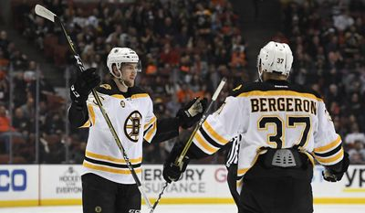 Boston Bruins defenseman Brandon Carlo, left, celebrates his goal with center Patrice Bergeron during the first period of the team's NHL hockey game against the Anaheim Ducks, Wednesday, Feb. 22, 2017, in Anaheim, Calif. (AP Photo/Mark J. Terrill)
