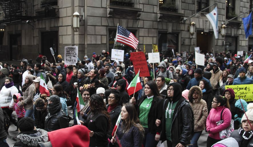 In this Feb. 16, 2017 file photo, hundreds of people take part in a protest and march aimed at President Donald Trump's nationwide efforts to crack down on immigration in Chicago. As Trump moves ahead with a nationwide immigration crackdown, school principals in Chicago have been given a simple order: Do not let federal immigration agents in without a criminal warrant. (Maria Cardona/Chicago Sun-Times via AP)