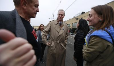 Democratic candidate for New Jersey governor Assemblyman John Wisniewski, D-Sayreville, N.J., center, looks on as Sen. Raymond J. Lesniak, D- Elizabeth, N.J., left, shows him a pro immigration slogan on his t-shirt during an immigration protest outside of a detention center, Thursday, Feb. 23, 2017, in Elizabeth, N.J. (AP Photo/Julio Cortez)