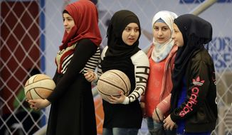 In this picture taken on Sunday, Feb. 19, 2017, Syrian refugee girls attend a basketball training session at a private sports club, southern Beirut, Lebanon. Every Sunday the gymnasium in Beirut echoes with the shouting and laughter of dozens of children, mostly Syrian refugees enjoying a rare escape from a grim and cloistered life in exile. The Sport 4 Development program, run by the U.N. children's agency, aims to bring 12,000 children, mostly Syrian refugees, to blacktops and turf pitches this year to teach the basics of soccer and basketball, and to ease the pain of war and displacement. (AP Photo/Hussein Malla)