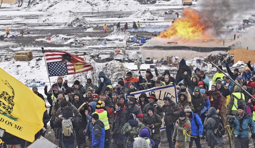 A fire set by protesters burns in the background as opponents of the Dakota Access pipeline leave their main protest camp Wednesday, Feb. 22, 2017, near Cannon Ball, N.D. Most of the pipeline opponents abandoned their protest camp Wednesday ahead of a government deadline to get off the federal land, and authorities moved to arrest some who defied the order in a final show of dissent. (Tom Stromme/The Bismarck Tribune via AP)