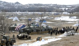 Law enforcement enters the Oceti Sakowin camp to begin arresting Dakota Access Pipeline protesters  in Morton County, Thursday, Feb. 23, 2017, near Cannon Ball, N.D. As the arrests were underway law enforcement personnel drove several large construction equipment into the camp to begin the cleanup process of razing tents and structures.  (Mike McCleary/The Bismarck Tribune via AP, Pool) ** FILE **