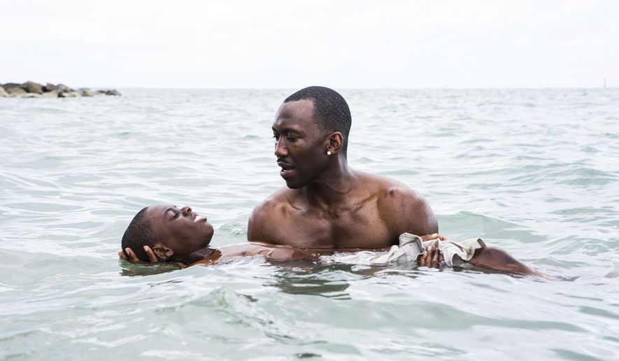 """This image released by A24 shows Alex Hibbert, foreground, and Mahershala Ali in a scene from the film, """"Moonlight."""" (David Bornfriend/A24 via AP)"""