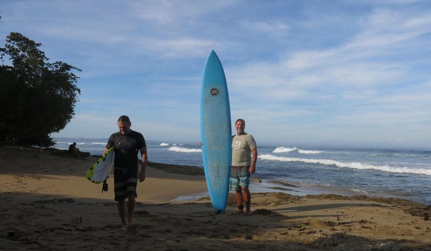 In this Feb. 16, 2017 photo, surfers Doug Lake, left, and Danny King pose for a picture at Wilderness Beach, in Aguadilla, a lush corner in northwest Puerto Rico that has remained largely untouched since Christopher Columbus landed there in his second voyage to the New World. The area could soon become the site of a $200 million development that is pitting environmentalists who seek to convert the land into a national park against those who say the Christopher Columbus Landing resort could create jobs, generate tourism and boost real estate prices amid an economic crisis. (AP Photo/Danica Coto)