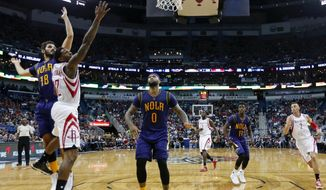 Houston Rockets guard Lou Williams (12) goes to the basket between New Orleans Pelicans forwards Omri Casspi (18) and DeMarcus Cousins (0) during the second half of an NBA basketball game in New Orleans, Thursday, Feb. 23, 2017. The Rockets won 129-99. (AP Photo/Gerald Herbert)