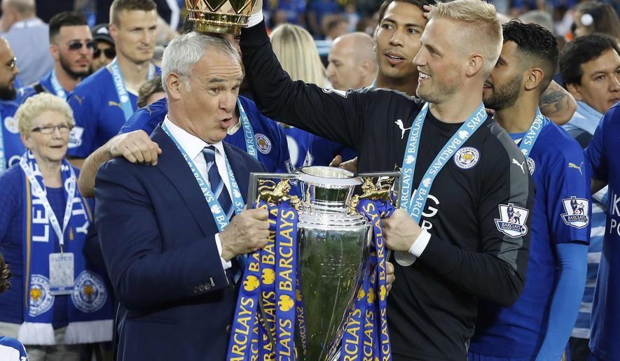 FILE - In this Saturday, May 7, 2016 file photo Leicester City team manager Claudio Ranieri has the crown of the trophy placed on his head by Leicester goalkeeper Kasper Schmeichel as they celebrate becoming the English Premier League soccer champions at King Power stadium in Leicester, England. Leicester City announced Thursday, Feb. 23, 2017 that they have sacked manager Claudio Ranieri less than a year after their incredible run to the Premier League title. (AP Photo/Matt Dunham, File)