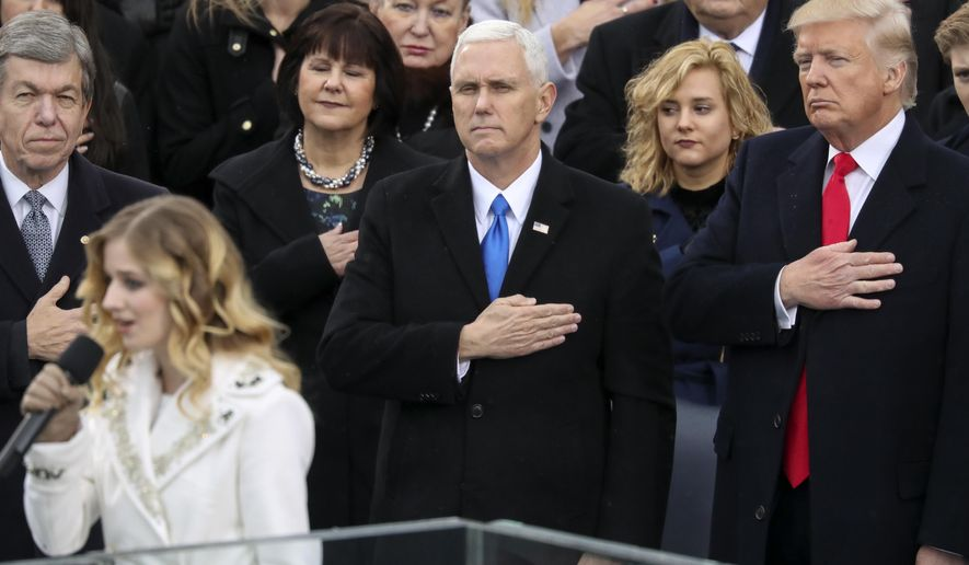 FILE - In this Jan. 20, 2017, file photo, Vice President Mike Pence and President Donald Trump listen to the singing of the national anthem by Jackie Evancho during the 58th Presidential Inauguration at the U.S. Capitol in Washington. Evancho asked Trump in a tweet on Feb. 22, 2017,   to meet with her and her transgender sister on transgender rights. (AP Photo/Andrew Harnik, File)