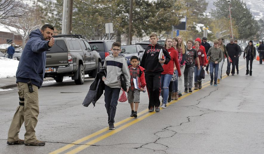 FILE - In this Dec. 1, 2016, file photo, a police officer directs students down the street following a school lockdown at Mueller Park Junior High after a student fired a gun into the ceiling, in Bountiful, Utah. A Utah teenager who pleaded guilty to firing the shotgun before being disarmed by his parents is set to be sentenced Thursday, Feb. 23, 2017. (AP Photo/Rick Bowmer, File)