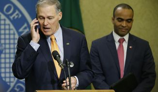 Washington Gov. Jay Inslee, left, briefly speaks into his phone after it rang during a news conference, Thursday, Feb. 23, 2017, at the Capitol in Olympia, Wash., as general counsel Nick Brown looks on at right. Inslee signed an executive order Thursday to ensure that state workers don't help carry out President Donald Trump's immigration policies. (AP Photo/Ted S. Warren)