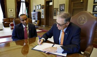 Washington Gov. Jay Inslee right, signs an executive order, Thursday, Feb. 23, 2017, in his office at the Capitol in Olympia, Wash., as general counsel Nick Brown looks on at left. The order ensures that state workers don't help carry out President Donald Trump's immigration policies. Trump has said he wants to expand the number of deportations of people in the country illegally, and Inslee said Thursday that his order reaffirms the state's commitment to tolerance and ensures that state workers roles are to provide services for residents and not to enforce immigration statutes. (AP Photo/Ted S. Warren)