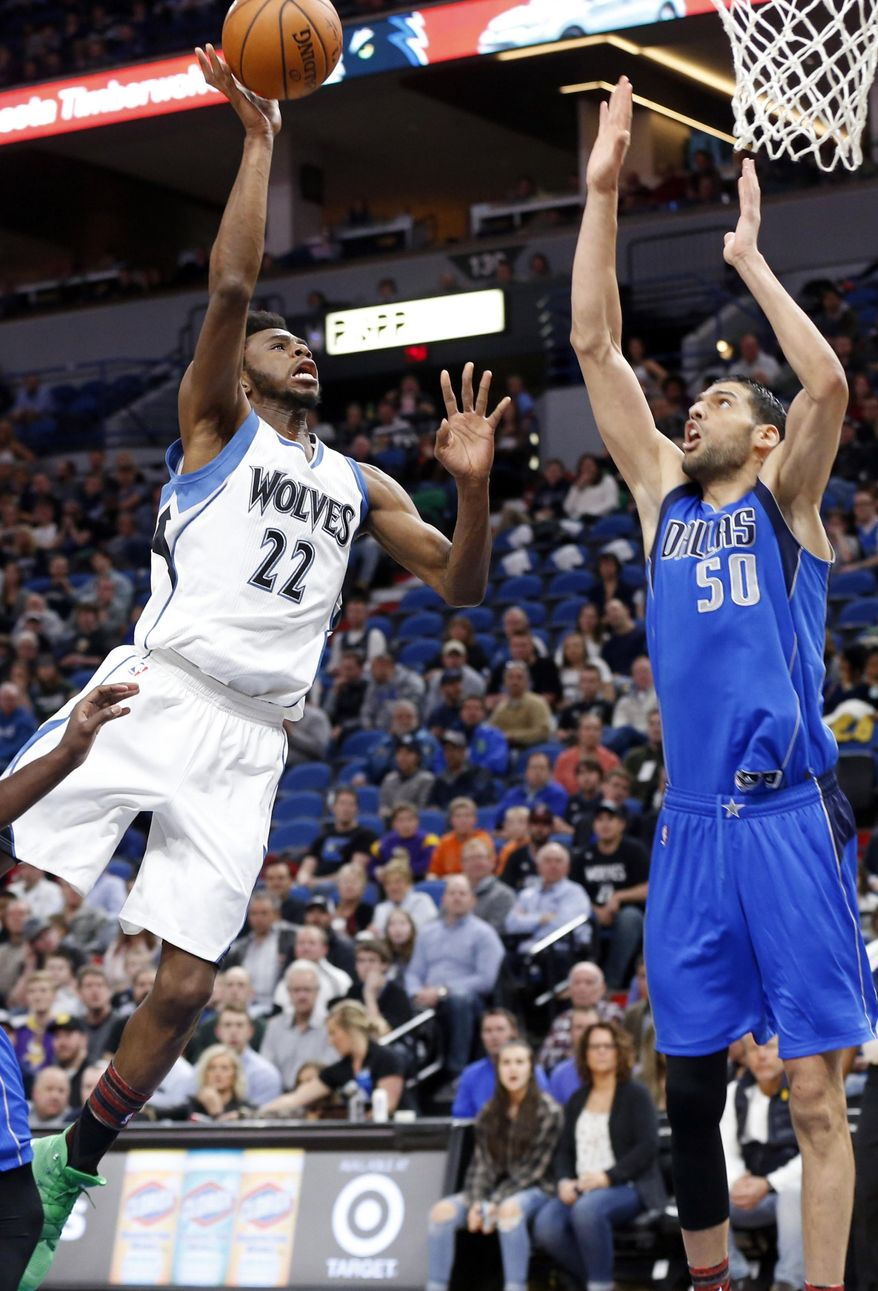 Minnesota Timberwolves' Andrew Wiggins, left, lays up as Dallas Mavericks' Salah Mejri, of Tunisia, defends during the first half of an NBA basketball game Friday, Feb. 24, 2017, in Minneapolis. (AP Photo/Jim Mone)