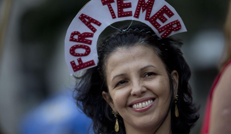 "A reveler wears a crown that reads in Portuguese: ""Out Temer"" during a carnival street party in Rio de Janeiro, Brazil, Friday, Feb. 24, 2017. Merrymakers took to the streets to protest Brazil's President Michel Temer. (AP Photo/Silvia Izquierdo)"