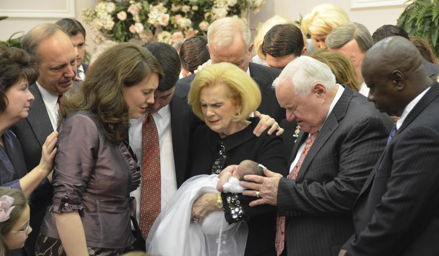 ADVANCE FOR USE MONDAY, FEB. 27, 2017 AT 1 A.M. EDT AND THEREAFTER-In this 2012 provided by a former member of the church, Word of Faith Fellowship leader Jane Whaley, center, holds a baby, accompanied by her husband, Sam, center right, and others during a ceremony in the church's compound in Spindale, N.C. From all over the world, they flocked to this tiny town in the foothills of the Blue Ridge Mountains, lured by promises of inner peace and eternal life. What many found instead: years of terror _ waged in the name of the Lord. (AP Photo)