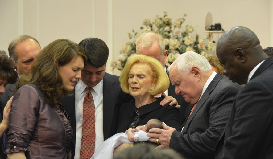 ADVANCE FOR USE MONDAY, FEB. 27, 2017 AT 1 A.M. EDT AND THEREAFTER-In this 2012 provided by a former member of the church, Word of Faith Fellowship leader Jane Whaley, center, holds a baby with her husband, Sam, center right, and others during a ceremony in the church's compound in Spindale, N.C. When it comes to relationships, marriage and sex, Word of Faith Fellowship members must follow strict and unusual rules _ or risk severe punishment, former members say (AP Photo)