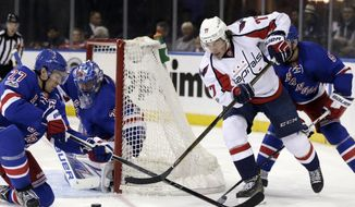 Washington Capitals' T.J. Oshie, second from right, tries to score past New York Rangers' Ryan McDonagh, left, and goalie Henrik Lundqvist during the third period of an NHL hockey game, Sunday, Feb. 19, 2017, in New York. (AP Photo/Seth Wenig)