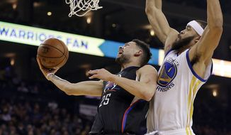 Los Angeles Clippers' Austin Rivers, left, lays up a shot past Golden State Warriors' JaVale McGee (1) during the first half of an NBA basketball game Thursday, Feb. 23, 2017, in Oakland, Calif. (AP Photo/Ben Margot)