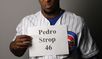 Chicago Cubs' Pedro Strop holds up his name during the team's photo day Tuesday, Feb. 21, 2017, in Mesa, Ariz. (AP Photo/Morry Gash)