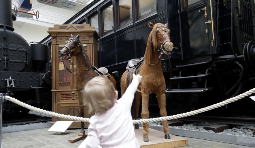 In this picture taken on Thursday, Feb. 23, 2017, a young girl looks at restored stuffed horses that were part of a historical carousel put on display at the National Technical Museum in Prague, Czech Republic. The museum acquired the carousel in 2004 from its private owners and had finally secured enough money to finance a major renovation project. (AP Photo/Petr David Josek)