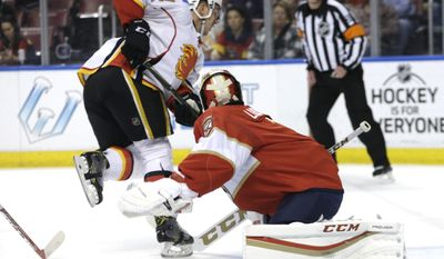 Calgary Flames center Mikael Backlund, left, shoots to score a goal against Florida Panthers goalie Roberto Luongo, right, during the first period of an NHL hockey game, Friday, Feb. 24, 2017, in Sunrise, Fla. (AP Photo/Lynne Sladky)