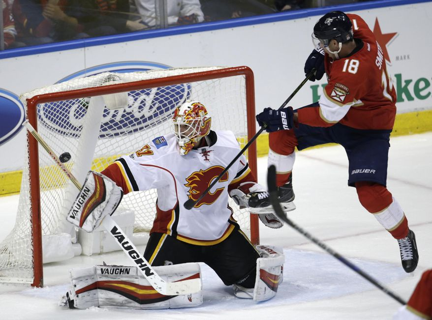 Calgary Flames goalie Chad Johnson (31) defends the goal as Florida Panthers right wing Reilly Smith (18) looks on during the third period of an NHL hockey game, Friday, Feb. 24, 2017, in Sunrise, Fla. (AP Photo/Lynne Sladky)