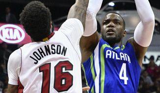 Atlanta Hawks forward Paul Millsap (4) shoots as Miami Heat forward James Johnson (16) defends during the first half of an NBA basketball game, Friday, Feb. 24, 2017, in Atlanta. (AP Photo/John Amis)