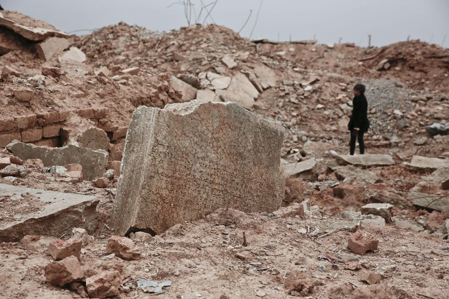 FILE - In this Wednesday, Dec. 14, 2016 file photo, a stone tablet with cuneiform writing is seen in the foreground as UNESCO's Iraq representative Louise Haxthausen documents the damage wreaked by the Islamic State. At a two-day UNESCO conference, Iraqi officials are asking for money and expertise to reclaim the cultural heritage that is on the verge of complete destruction by the Islamic State group (AP Photo/Maya Alleruzzo, File)