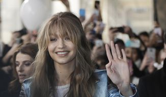 Model Gigi Hadid waves as she arrives to attend a presentation for Tommy Hilfiger women's Fall-Winter 2017-18 collection, in Milan, Italy, Friday, Feb. 24, 2017. (AP Photo/Luca Bruno).
