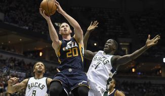 Utah Jazz's Gordon Hayward (20) shoots  against Milwaukee Bucks' Thon Maker (7) and Michael Beasley (9) in the second half during an NBA basketball game Friday, Feb. 24, 2017, in Milwaukee. (AP Photo/Benny Sieu)