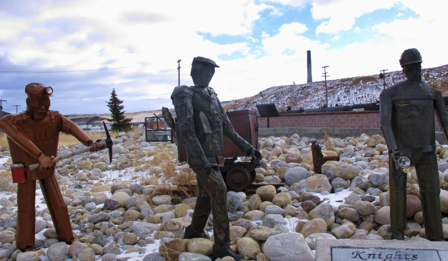 This Dec. 13, 2016 shows the former Anaconda smelter smokestack behind sculptures of miners at the Anaconda Smelter Stack State Park viewing area in Anaconda, Mont. Residents in the nearby community of Opportunity are suing for the right to clean the toxic metals left by the smelter from their yards and claim federal environmental officials and the smelter's owner have botched a 34-year cleanup. (AP Photo/Matt Volz)
