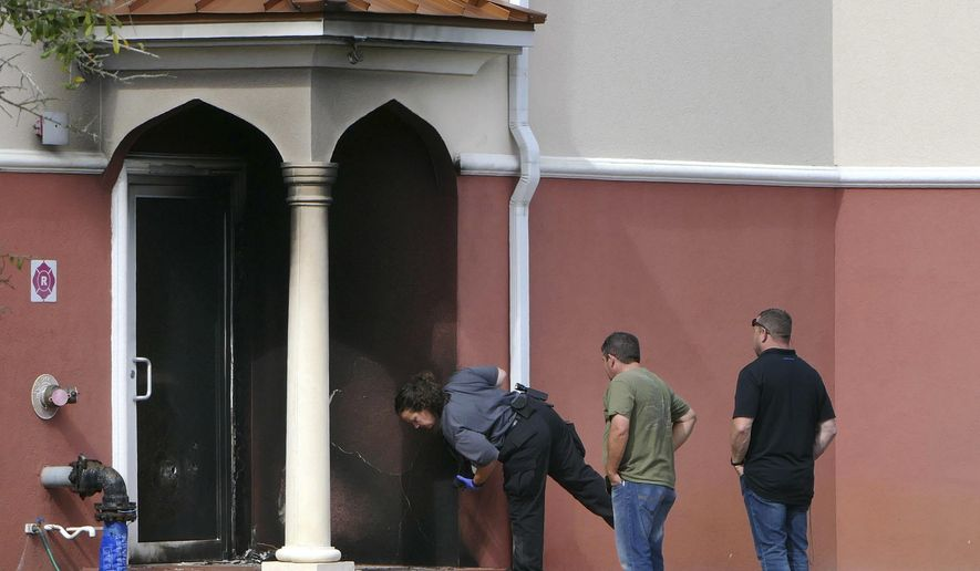 Fire officials inspect a side door where an arson took place at the Daarus Salaam Mosque in Thonotosassa, Fla.,  Friday, Feb. 24, 2017. (James Borchuck/The Tampa Bay Times via AP)