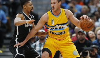 Denver Nuggets forward Danilo Gallinari, right, of Italy, works the ball inside for a shot as Brooklyn Nets guard Spencer Dinwiddie defends in the second half of an NBA basketball game Friday, Feb. 24, 2017, in Denver. (AP Photo/David Zalubowski)