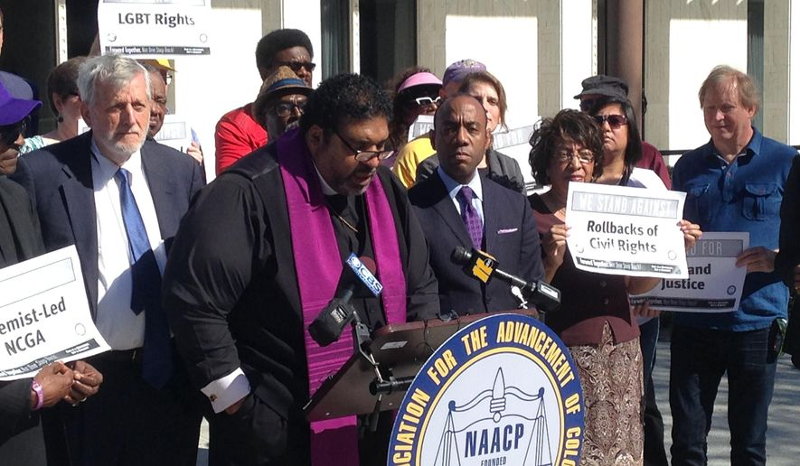 North Carolina's NAACP leader The Rev. William Barber speaks at a news conference on Friday, Feb. 24, 2017, in Raleigh, N.C.,  while the national NAACP president Cornell Brooks looks on. The two were announcing the first steps in a national economic boycott of the state over conservative policies including a law limiting LGBT rights. (AP Photo/Jonathan Drew)