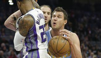 Denver Nuggets forward Danilo Gallinari, right, is fouled by Sacramento Kings guard Ben McLemore, left, as Kings center Kosta Koufos, center, looks on during the first half of an NBA basketball game Thursday, Feb. 23, 2017, in Sacramento, Calif. (AP Photo/Rich Pedroncelli)