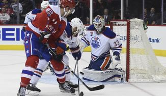 Edmonton Oilers goalie Cam Talbot (33) eyes the puck shot by Washington Capitals center Zach Sanford (82) as Edmonton Oilers center Mark Letestu (55) defends during the second period of their NHL hockey game, Friday, Feb. 24, 2017, in Washington. (AP Photo/Molly Riley)