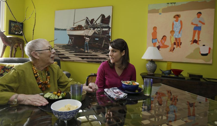 In this Friday, Feb. 17, 2017 photo, Laura Berick, left, a retired art dealer, has lunch with Justine Myers at Berick's home in Judson Manor, in Cleveland. In a research project, graduate-level students live among residents of the Judson Manor retirement home. The study looks at the impact of isolation and loneliness, aging and stereotypes of retirees by students and vice versa. Myers is an artist-in-residence at Judson Park.  (AP Photo/Tony Dejak)
