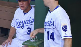 This photo taken Aug. 18, 2016 shows Kansas City Royals' Billy Burns bringing out Rally Mantis Jr in his new cage past manager Ned Yost before the start of Thursday's baseball game against the Minnesota Twins  in Kansas City, Mo. Acquired last July 30 for Brett Eibner, Burns became caretaker of a rally praying mantis when the Royals went on a hot streak. Burns researched on how to tend to the mantis alive, purchased a glass cage with foliage and gave him insects to eat. (John Sleezer/The Kansas City Star via AP)