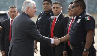 U.S. Secretary of State Rex Tillerson shakes hands with police officers and security personnel as he boards a plane to depart at Benito Juarez international Airport in Mexico City, Thursday, Feb. 23, 2017. (Carlos Barria/Pool Image via AP